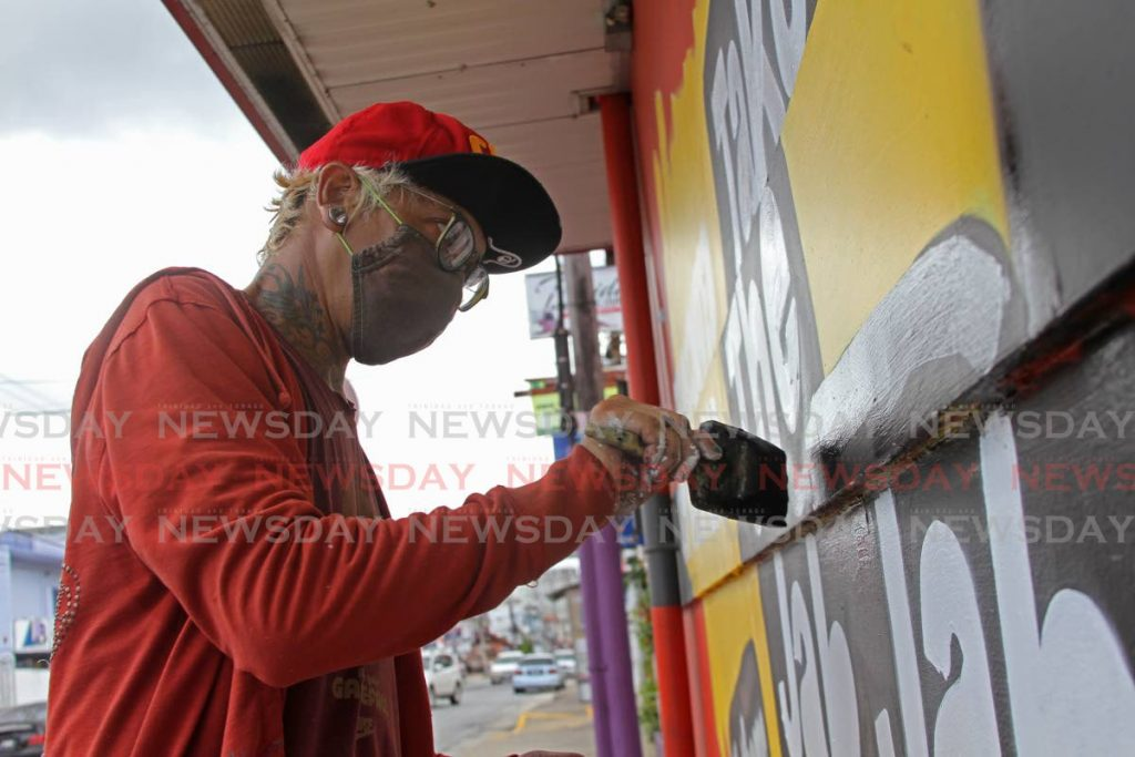 Graffiti artist Zinnia Cheewah puts finishing touches on the Take the Jab Jab mural on the wall of Mario's Pizzeria. Cheewah is also working on a mural with other artists in memory of five men killed by police in Morvant in 2020. - Photo by Marvin Hamilton