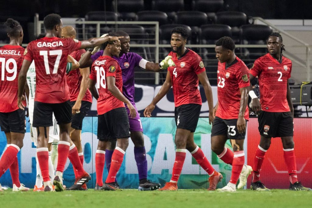 TT goalkeeper Marvin Phillip (C) speaks with defender Triston hodge (3rd L) during the first half of their Concacaf Gold Cup group stage match against Mexico at the AT&T stadium in Arlington, Texas on Saturday. TT take on El Salvador on Wednesday, in Texas. -