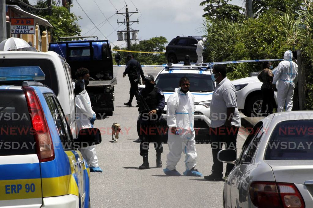 File photo: Police and crime scene investigators crowd near George Boyce Recreation Grounds and Ridgeland Park Road on the Arima Old Road, Clever Heights, Mausica, where three bodies were found.  Photo by Roger Jacob