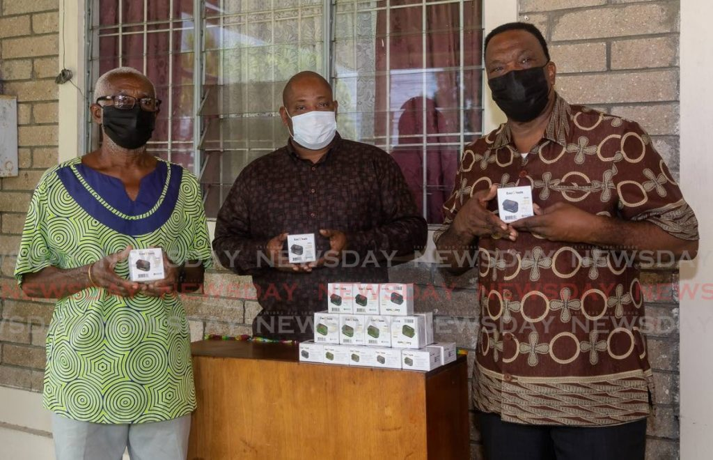 FILE photo: Nigel Walcott, centre, of Island Living Co Ltd donates oximeters to Rudolph Hypolite, left, and Harrace Barton, right, both of the Tobago Association of The Elderly (TATE). Island Living is part of a network of institutions caring for senior citizens. - David Reid