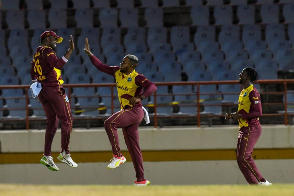 Darren Bravo (left), Fabian Allen (centre) and Hayden Walsh Jr. of West Indies celebrate the dismissal of Aaron Finch of Australia during the 5th and final T20 International between Australia and West Indies at the Darren Sammy Cricket Ground, Gros Islet, St Lucia, on July 16, 2021. (AFP PHOTO) -