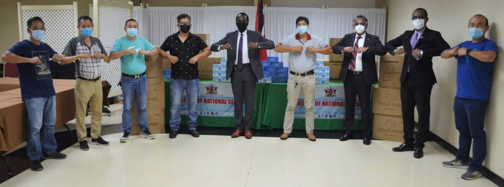 Minister of National Security Fitzgerald Hinds, ministry officials and members of the Chinese business community at the handover of 68,000 face masks for the Ministry of National Security.   - Photo courtesy National Security Ministry
