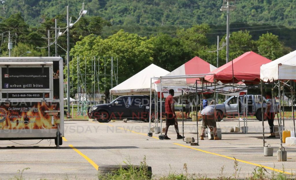 A few people check tents at the site of the food village on Saturday at Eddie Hart Grounds, Tunapuna which reopens on Tuesday. - Photo by Sureash Cholai
