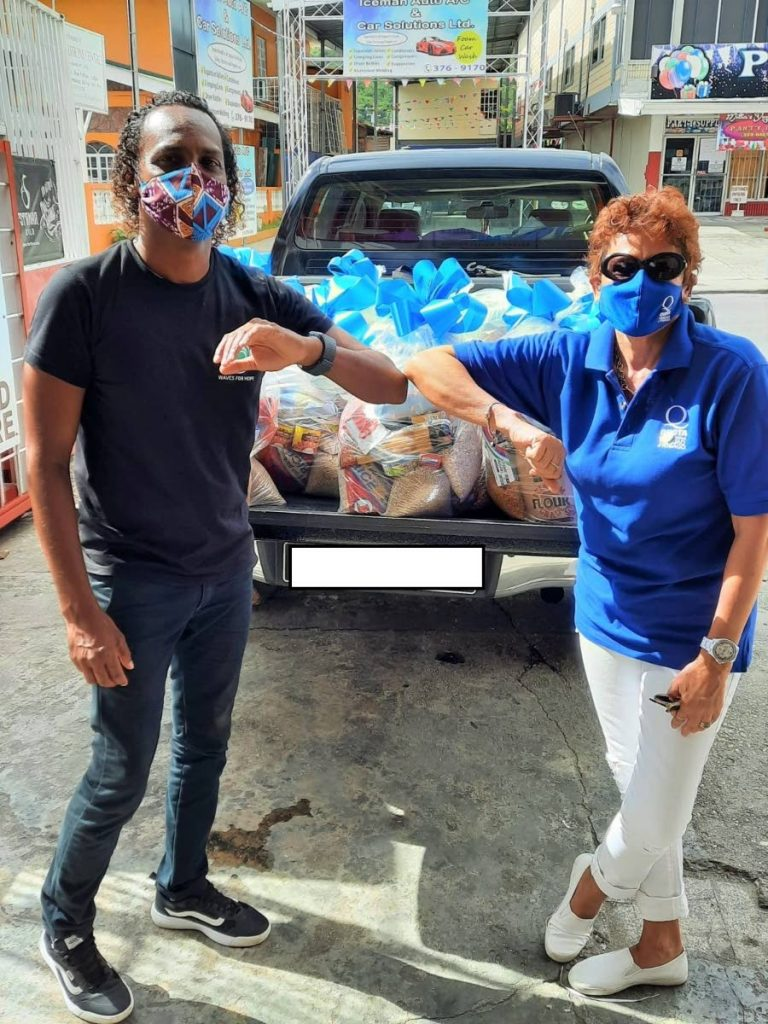 QuotaTT's Margaret Loregnard presents hampers to a representative of Waves for Hope of the Rampanalgas community in Toco.   -
