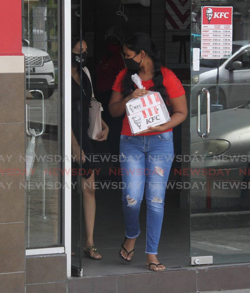 This woman took the opportunity to be among the first people to purchase KFC at the Couva Shopping Complex on Monday, when restaurants and street food vendors were allowed to re-open. Photo by Angelo Marcelle