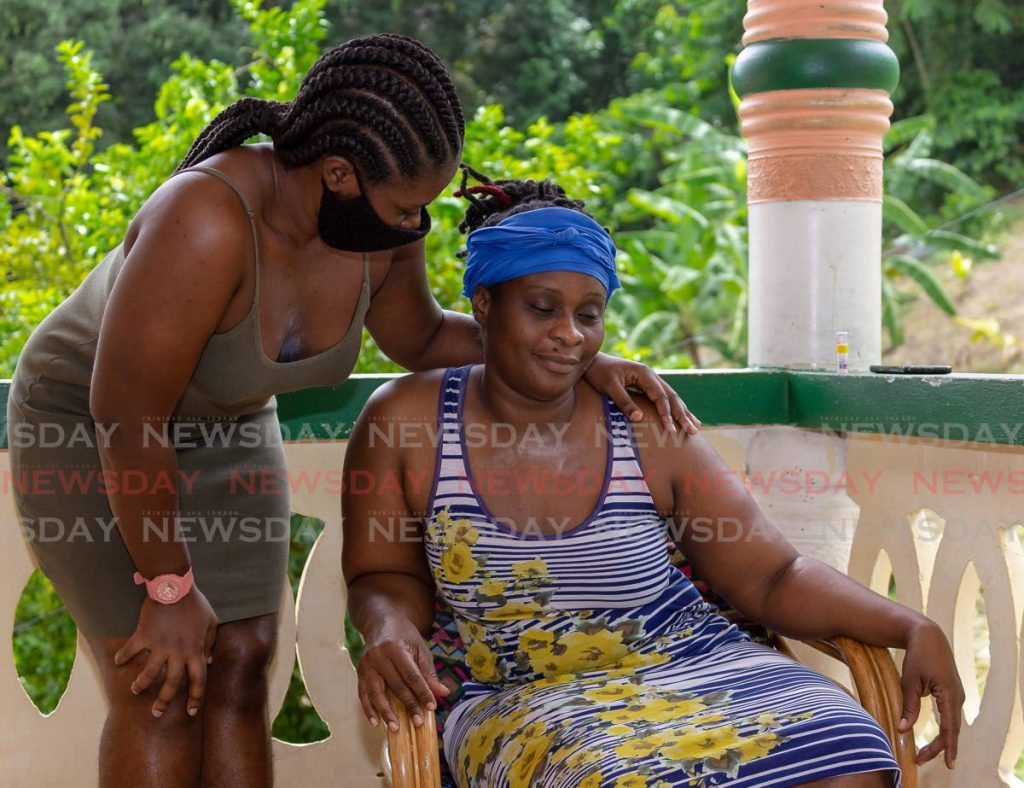 Nkosi Kerr's mother Charlene Jack is consoled by her cousin Afiya Orr at her Back Street, Mt St George, Tobago home on Monday. - David Reid