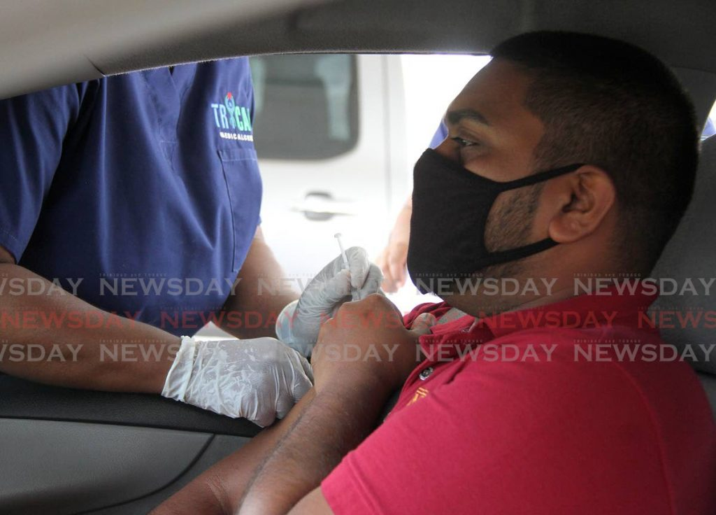A man receives his covid19 vaccine at the mass drive-through facility at Ato Boldon Stadium, Couva on Tuesday. The new option started on Monday. Photo by  Angelo Marcelle