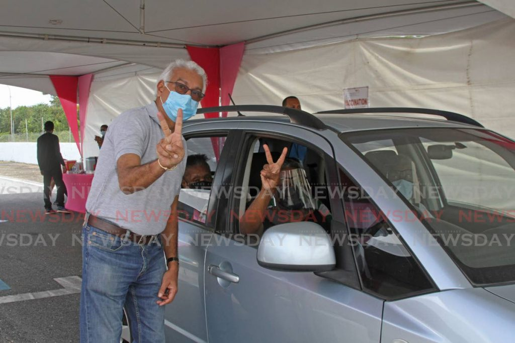 A driver who got his covid19 vaccine at the Wallerfield international raceway mass vaccination site on Wednesday, poses with Health Minister Terrence Deyalsingh. - Photo by Marvin Hamilton