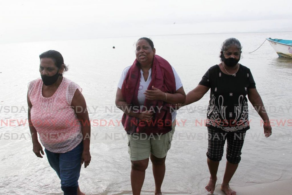 Sandra Garib (centre) is walked onto the shore at the Carli Bay fishing depot after praying for the safe return of her son Navindra