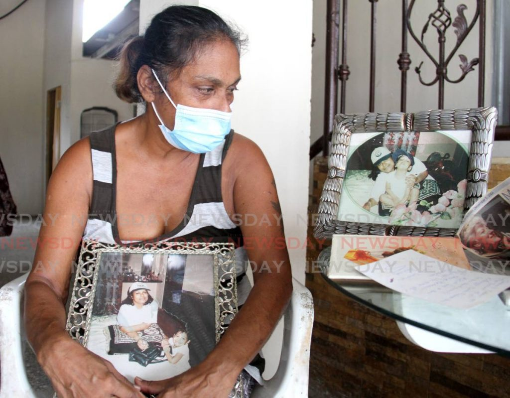 Pauline Bharat holds and looks at photographs of her with her son Sean Luke at her home in Orange Valley on Friday.  - Photo by Ayanna Kinsale