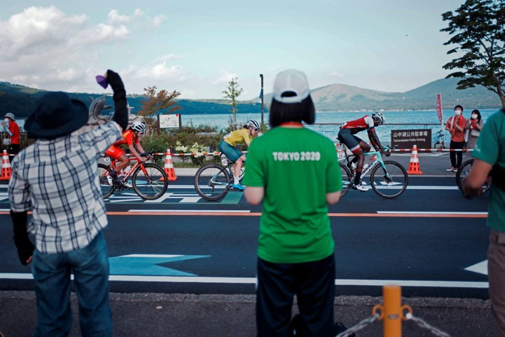 Fans watch as Teniel Campbell of Trinidad And Tobago (R), Amanda Spratt of Australia (C), and Jiajun Sun of China (L), compete during the women's cycling road race at the 2020 Summer Olympics, on Sunday, in Oyama, Japan. (AP Photo) -