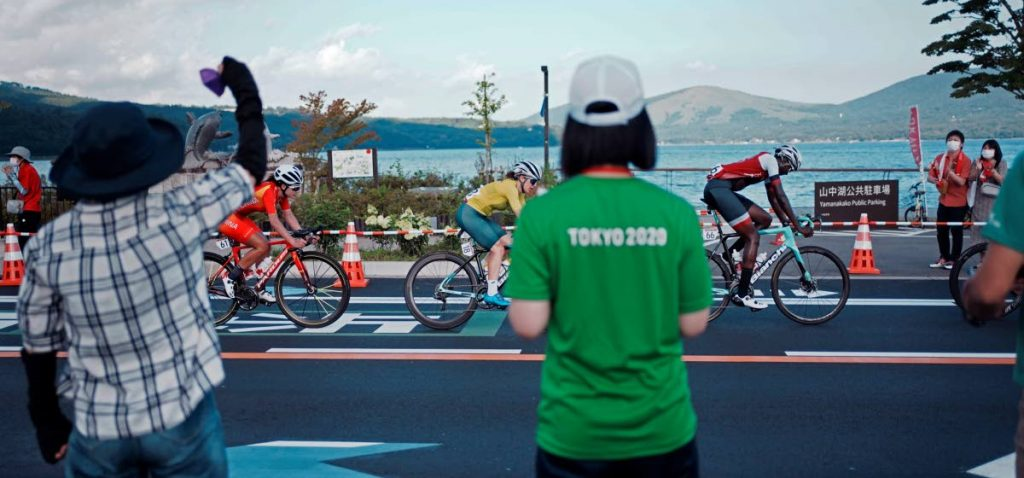 Fans watch as Teniel Campbell of Trinidad and Tobago, right, Amanda Spratt of Australia, centre, and Jiajun Sun of China, left, compete during the women's cycling road race at the 2020 Summer Olympics, Sunday, in Oyama, Japan. (AP) -