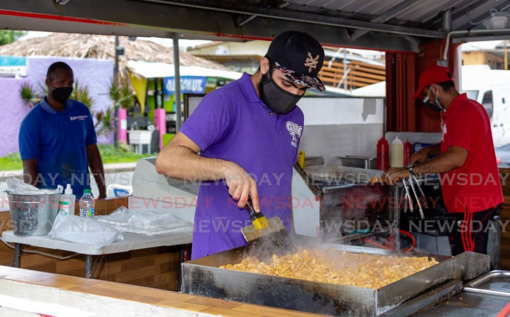 Zaref Deeb, front, manager of Gyro King, grills chicken at his restaurant in Crown Point last Thursday. Fast food lovers were back at their favourite spots after the Prime Minister announced food outlets were permitted to reopen. PHOTO BY DAVID REID -