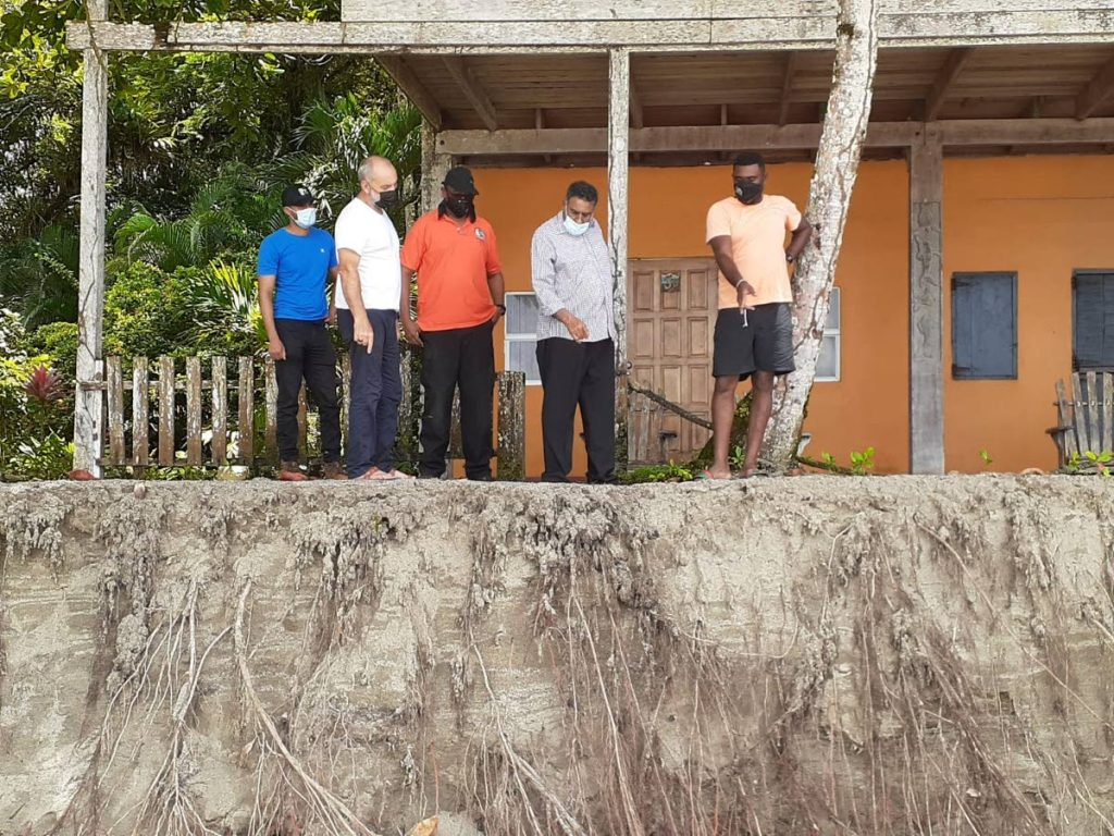 PNM councillor for Toco/Fishing Pond and officials of the Sangre Grande Regional Corporation's disater management unit look at the erosion behind the Mt Plaisir Estate Hotel in Grande Riviere on Sunday. -