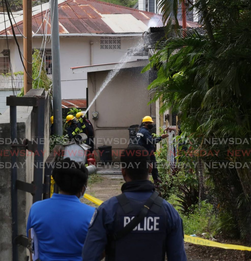 Fireman and police at the scene where three children perished in a house fire at No 1 Rookery Nook in Maraval. Photo by Sureash Cholai