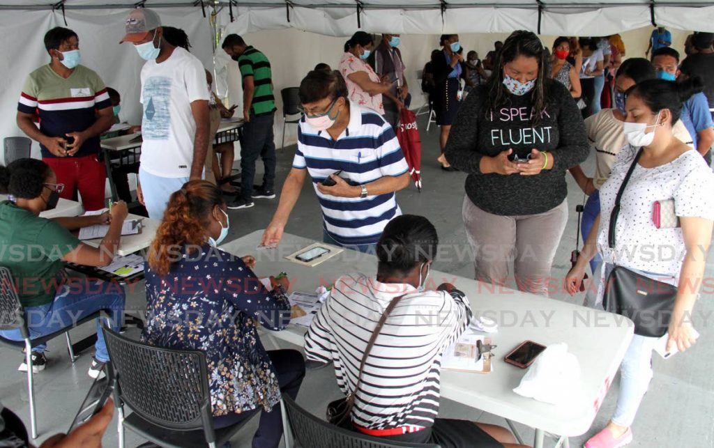 In this July 26 file photo, members of the public register before getting vaccinated at the Southern Academy of the Performing Arts (SAPA) in San Fernando.  Photo by Ayanna Kinsale