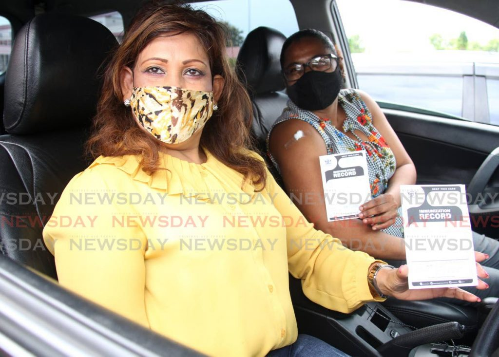 Salisha Mohammed and her friend Cindy Ram display their vaccination cards while waiting in their vehicle at the car park designated for observations at the vaccination drive-through facility at the Ato Boldon Stadium in Couva.   Photo by Ayanna Kinsale