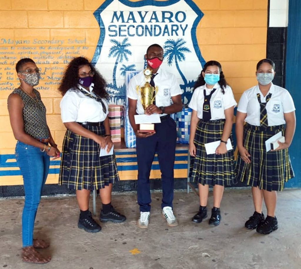 Arvolon Wilson Smith, founder and president of The Black Deer Foundation, shares a proud moment with the Mayaro Secondary School team who won the debate finals in the bpTT Schools' Environmental Awareness Competition. -