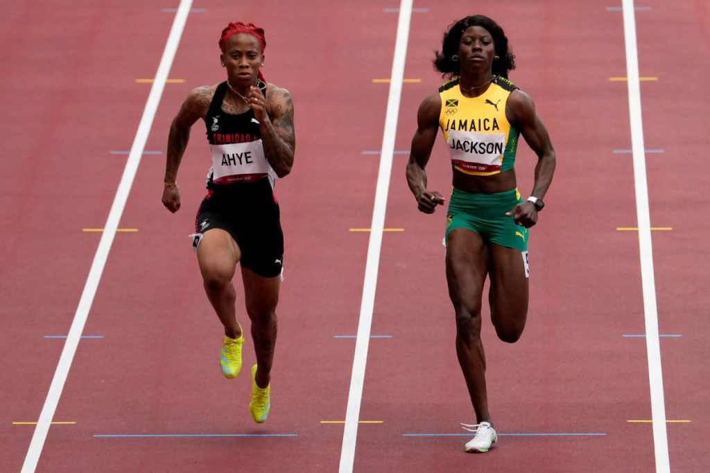 Michelle-Lee Ahye, left, of Trinidad and Tobago, wins a heat in the women's 100m event at the 2020 Summer Olympics, Friday, in Tokyo. (AP Photo) -