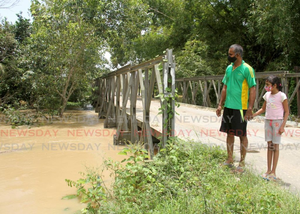 Azad Ali and his daughter Zaria looks on at as water flows through the South Oropouche River in Barrackpore, Friday. - AYANNA KINSALE