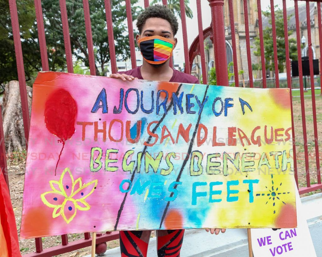 A member of the LGBTQ+ community holds a sign during Pride TT launch of Pride month in Port of Spain on June 26, 2020. - Photo by Jeff Mayers