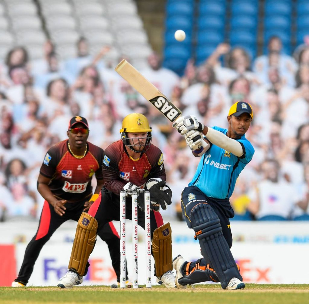 In this Sep 10, 2020 file photo, Mark Deyal (right) of St Lucia Zouks (Kings) hits a six as Trinbago Knight Riders' Tim Seifert (centre) and Dwayne Bravo watch during the teams' Hero Caribbean Premier League final, at the Brian Lara Cricket Academy in Tarouba.  (Photo by CPL T20 ) -