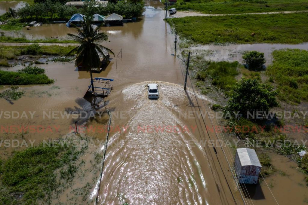 A motorists manoeuvres his car through the flood waters that covered parts of Suchit Trace, Penal on July 30. - Jeff K. Mayers