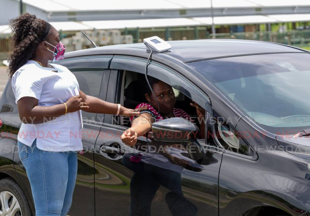 Regional nurse Carica Douglas checks the blood pressure of a woman before she is cleared for the Sinopharm vaccine at the drive-through vaccination site at Shaw Park on Saturday. - Photo by David Reid