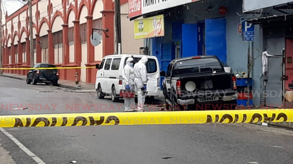 Crime Scene Investigators look at a black Nissan Navarra belonging to a man who was shot on George Street on Wednesday morning.  - Photo by Shane Superville