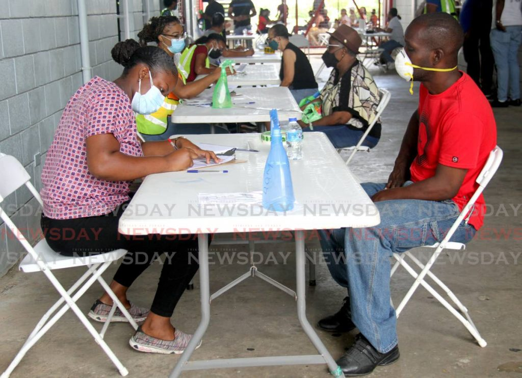 Volunteers register members of the public for vaccination at the Larry Gomes Stadium, Arima on Saturday. - PHOTO BY AYANNA KINSALE