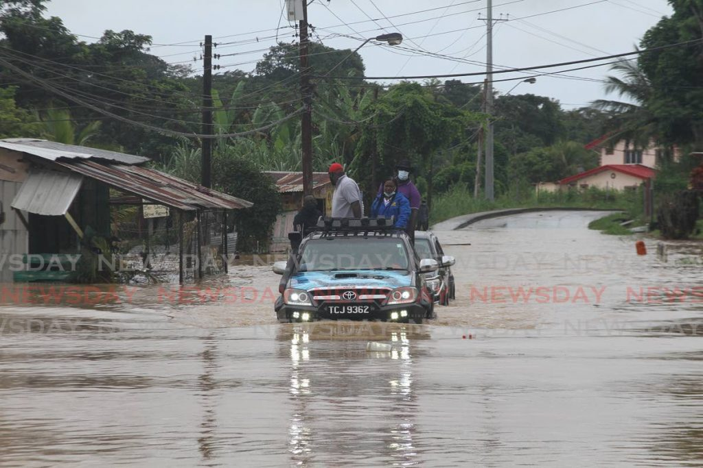 Point Fortin MP Kennedy Richards Jr drives through flood waters in Rancho Quemado after heavy rain associated with Tropical Storm Grace devastated the community on Sunday. - Marvin Hamilton