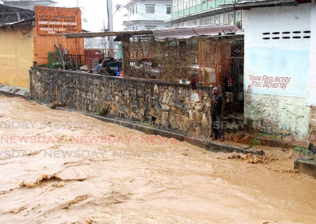 A man looks on with worry at the water levels of the East Dry River in Port of Spain as it threatened to burst its banks after heavy rain brought on by the passage of Tropical Story Grace on Sunday. - AYANNA KINSALE