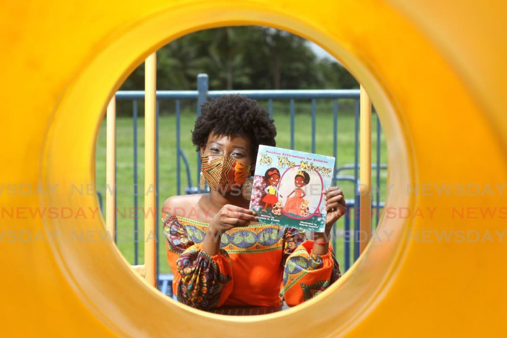 Djennicia Francis with her book In the Mirror which she wrote to help children feel good about themselves. - Photo by Marvin Hamilton
