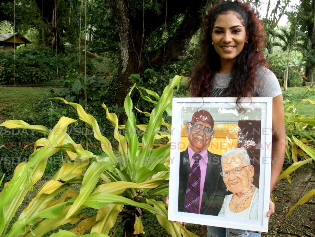 Mikaela Jodhan with one her portraits at Lopinot Historial Complex.  - Photo by Ayanna Kinsale