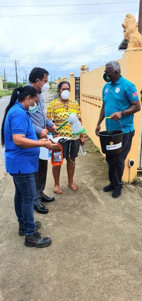 Sieunarine Coosal, chairman of Capital Campaign Cabinet Habitat for Humanity, and councilor Samuel Sankar meet residents of Kelly Village on Tuesday. - Photo courtesy Samuel Sankar