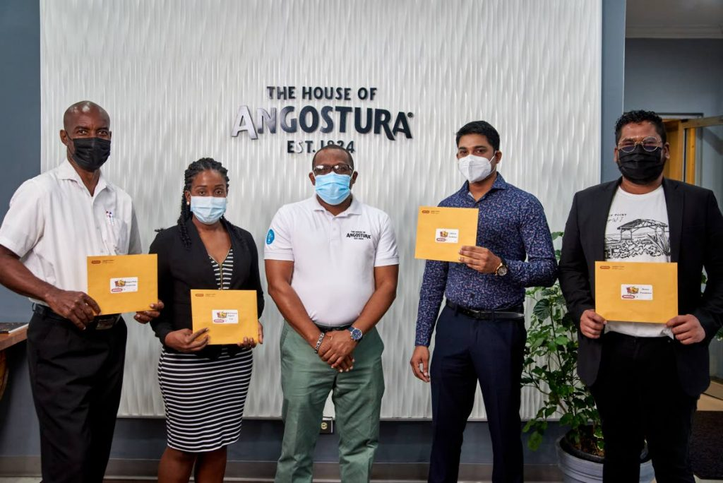 Angostura's acting CEO Ian Forbes (centre) with Chinapoo Police Youth Club chairman Eloy Burge (first from left), TTPS central division support officer, Dafina Tyson, Smile Foundation board member Afzal Khan, and Heroes Foundation CEO Lawrence Arjoon.  - Photo courtesy Angostura