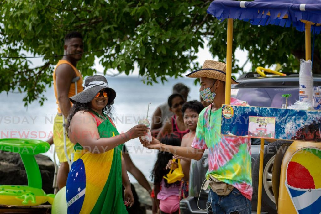Vendor Anthony Hildinger, right, offers a snow cone to a customer at Pigeon Point Beach, Tobago on August 16, 2020. File photo/David Reid   -
