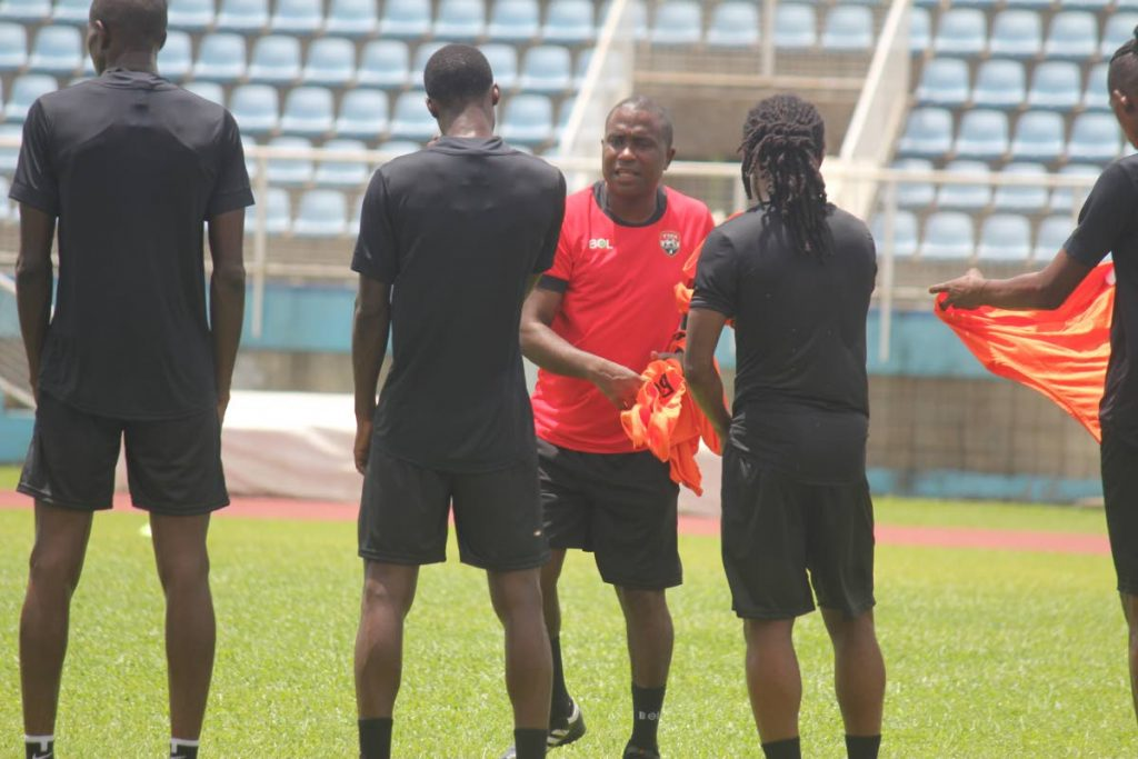 In this file photo, national coach Angus Eve gives out bibs at his first training session at the Ato Boldon Stadium in Couva.  - TTFA