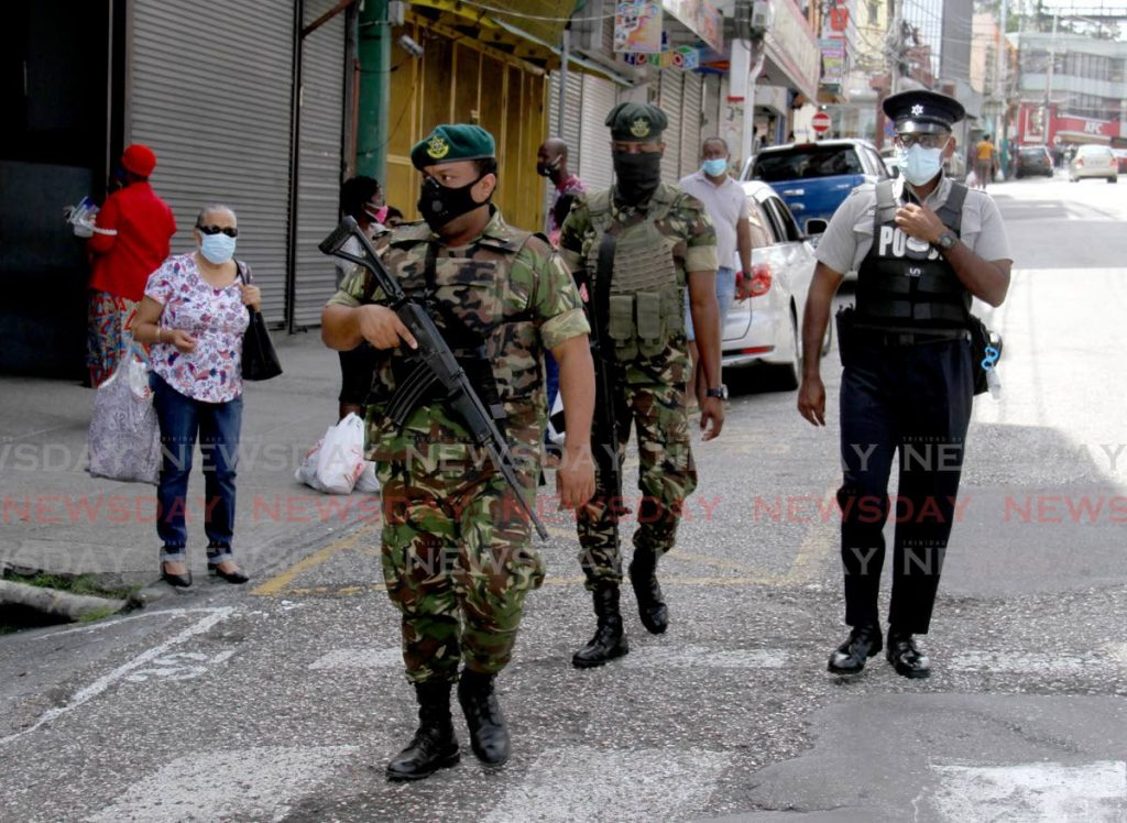 Mask-wearing soldiers and a policeman on patrol in San Fernando on June 29.  - PHOTO BY AYANNA KINSALE