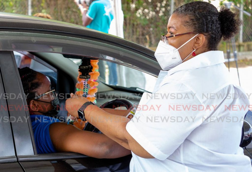 FILE PHOTO: Primary care nurse manager Kathy-Ann Ottley administers a dose of Sinopharm vaccine to a woman at the Shaw Park drive-through vaccination site. -
