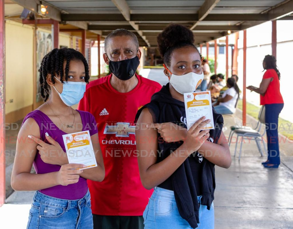 In this file photo, Tonya Wilson, 14, left and her best friend A'niah Taitt, 14, show their vaccination cards after receiving the Pfizer covid19 vaccine recently at Signal Hill Secondary School. Present to supervise was Tonya's father Nigel Wilson. - PHOTO BY DAVID REID