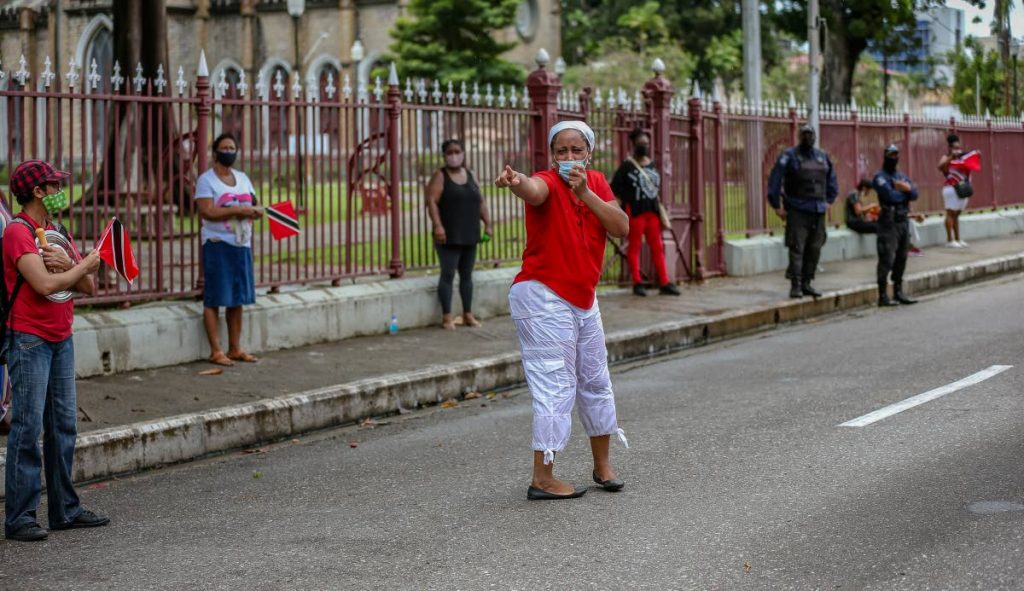 A protester in front of the Red House in Port of Spain recently, shares her disgust with Government's decision to vaccinate children. - File photo/Jeff Mayers