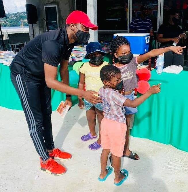 PDP deputy leader Farley Augustine assists three children at Tuesday's book drive in John Dial.