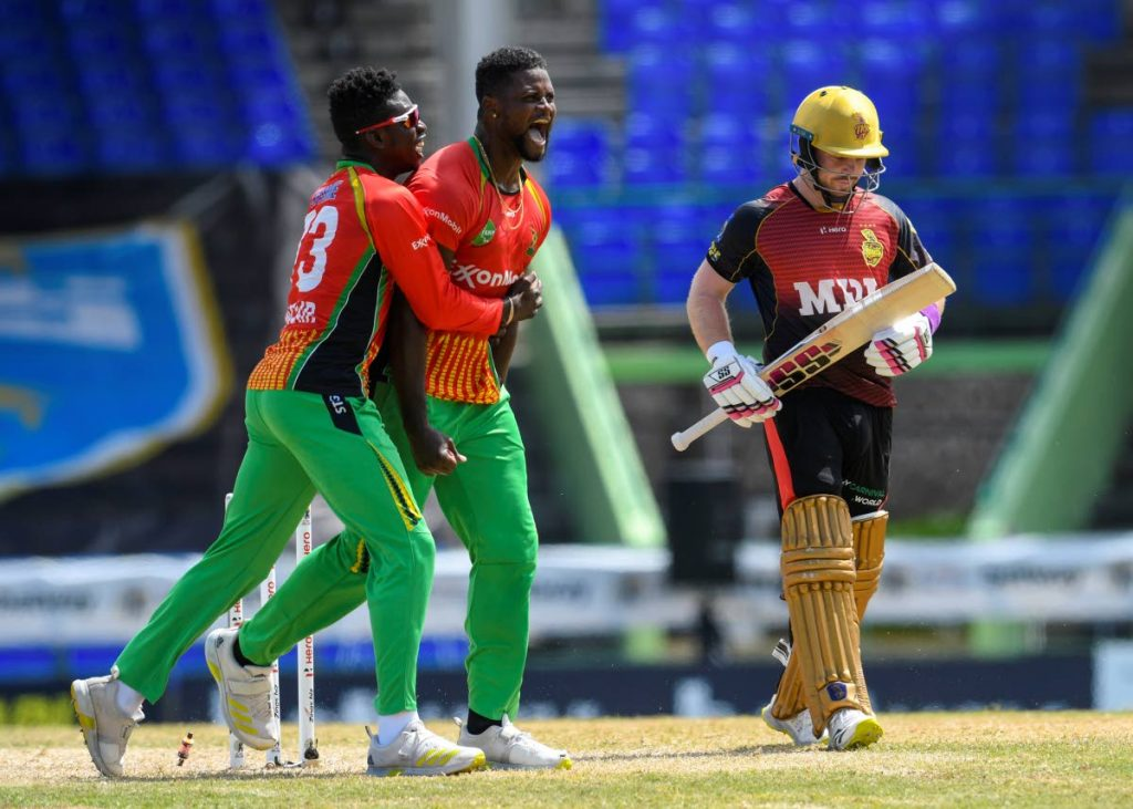 Romario Shepherd (centre) and Kevin Sinclair (left) of Guyana Amazon Warriors celebrate winning against the Trinbago Knight Riders in the super over during the 2021 Hero Caribbean Premier League match 11 at Warner Park Sporting Complex on Wednesday. At right, TKR's Tim Seifert walks towards the pavillion. - Photo courtesy CPL T20