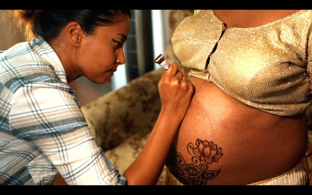 Aneesa Karim, body art professional, applying henna to the belly of a pregnant woman. -
