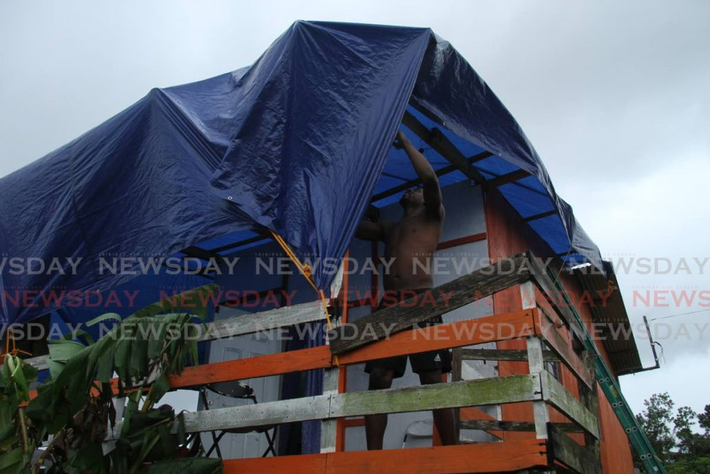 COVERING UP: Kynu Frederick of Hawk Ave, Warden Rd, Point Fortin tightens a tarpaulin over his house on Friday after his roof was blown off by hight winds on Thursday night. - AYANNA KINSALE