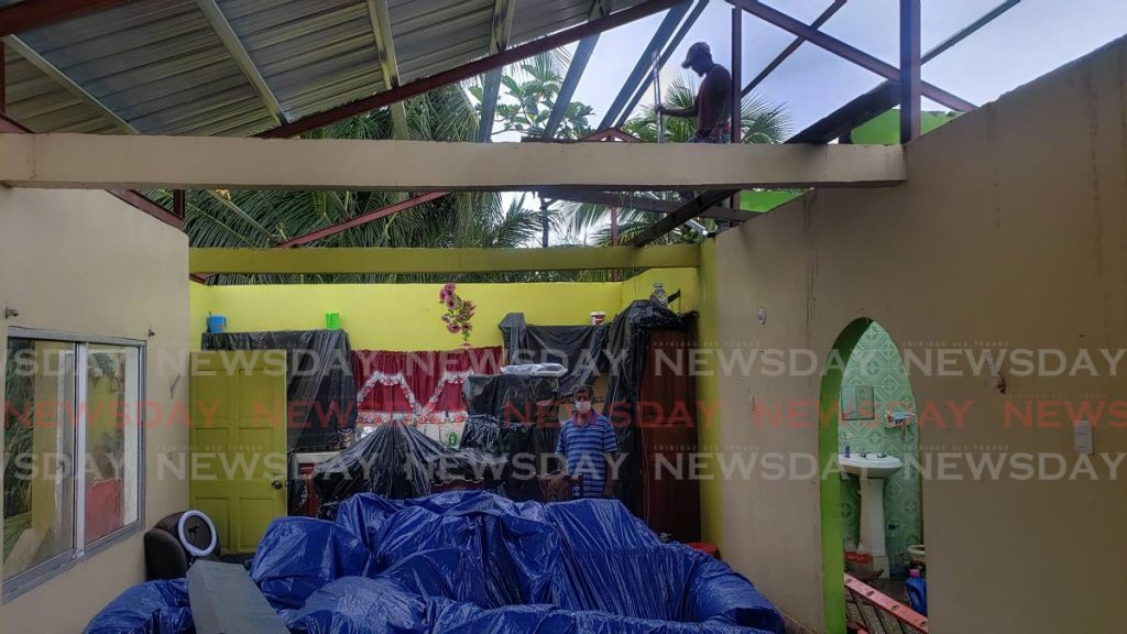 Hazel Suchit stands in his living while workmen repair the roof of his home in Fishing Pond, Sangre Grande on Saturday after strong gusts blew it off the house on Thursday night. - Photo by Roger Jacob.