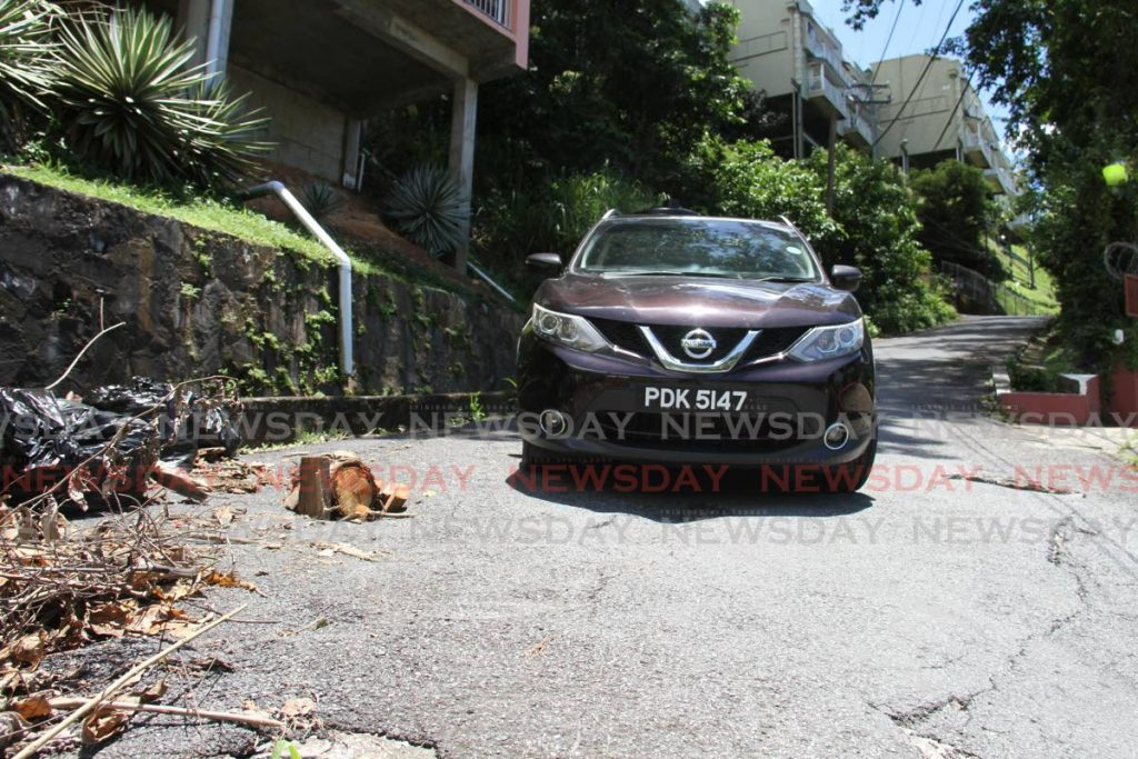 A driver manoeuvres their car around a hole filled with wood (on the left) on Irish Trace, Glencoe, on Monday. - Ayanna Kinsale