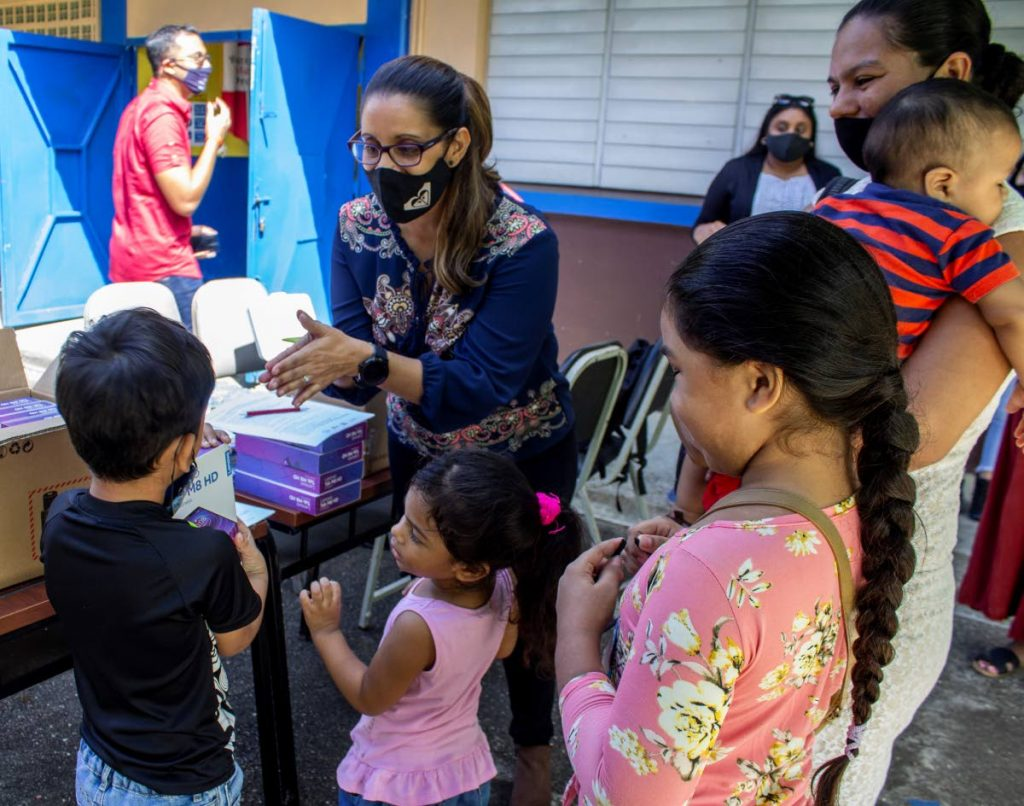 Migrant children receive tablets from an Equal Place representative. PHOTO COURTESY UNHCR -