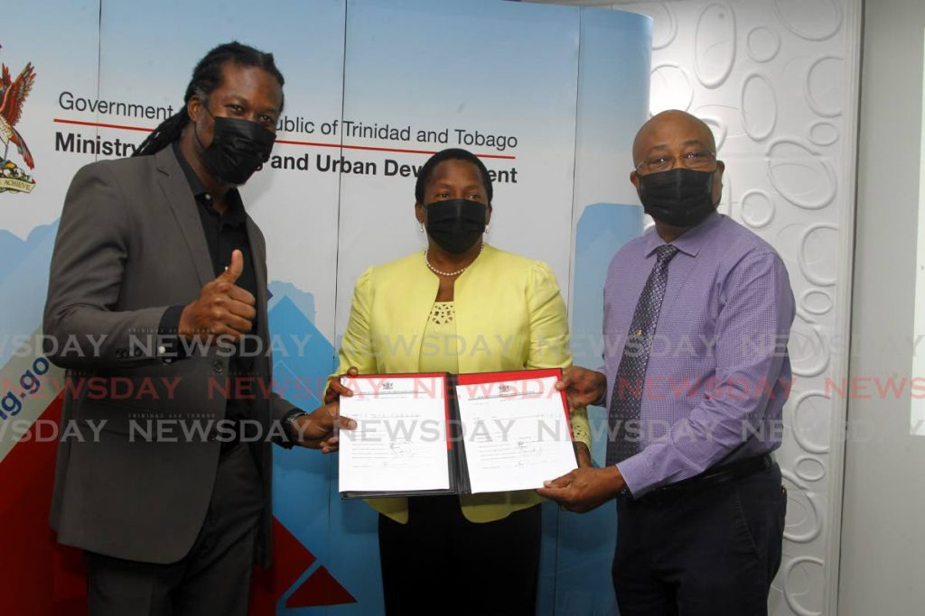 Minister in the Ministry of Housing Adrian Leonce, Housing Minister Penelope Beckles, and Wayne Innis, chairman of the Land Settlement Agency hold the official results of the draw at the HDC on Tuesday.    - ROGER JACOB